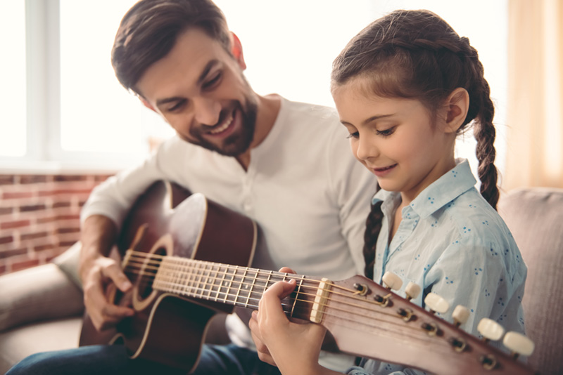 father teaching his daughter to play the guitar